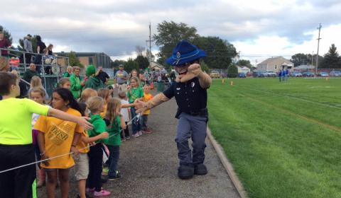An Officer Mascot gives high fives to children in crowd