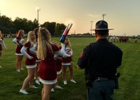 high school cheerleaders on football field with patrol officer standing nearby
