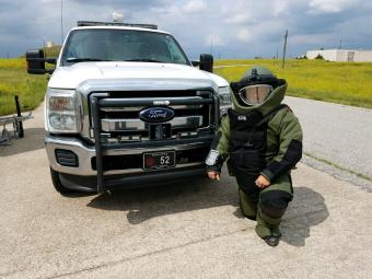 officer in bomb squad body armor next to truck