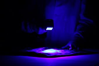 examiner using UV light on fabric