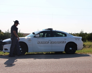 officer standing next to white patrol vehicle